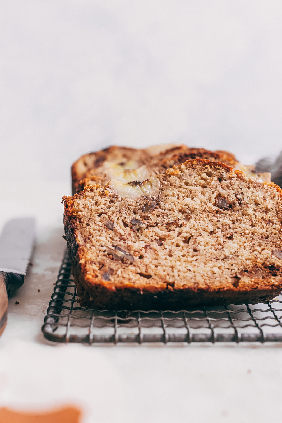 slices of banana bread on trivet with a bread knife on white marble