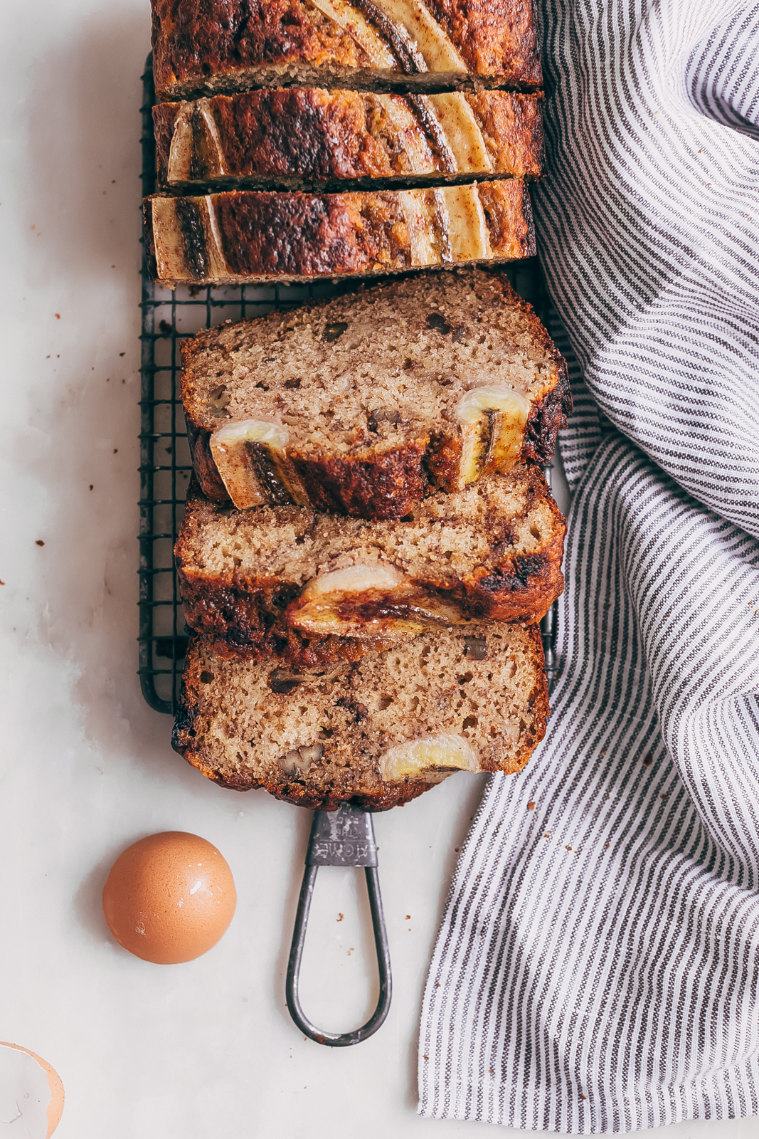 slices of pecan banana bread on trivet with striped napkin on white marble