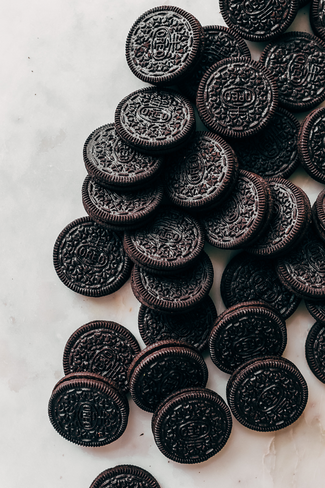 cascading Oreo cookies on white marble surface