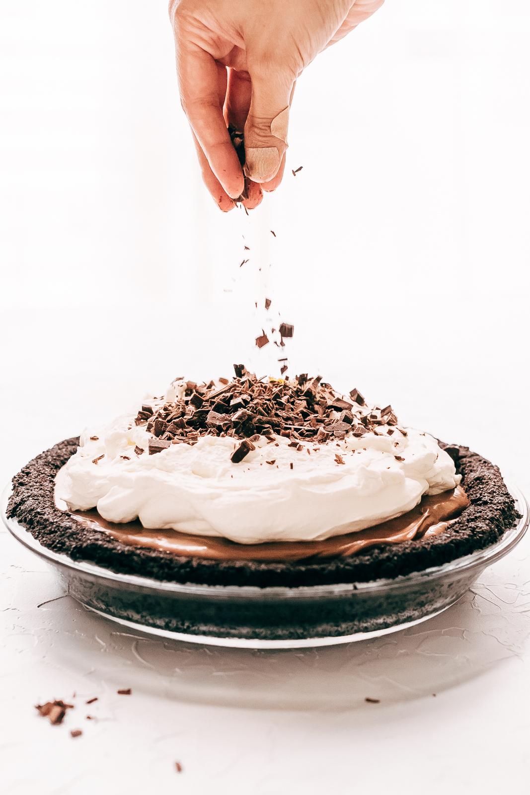 sprinkling chocolate shavings on Nutella Pie