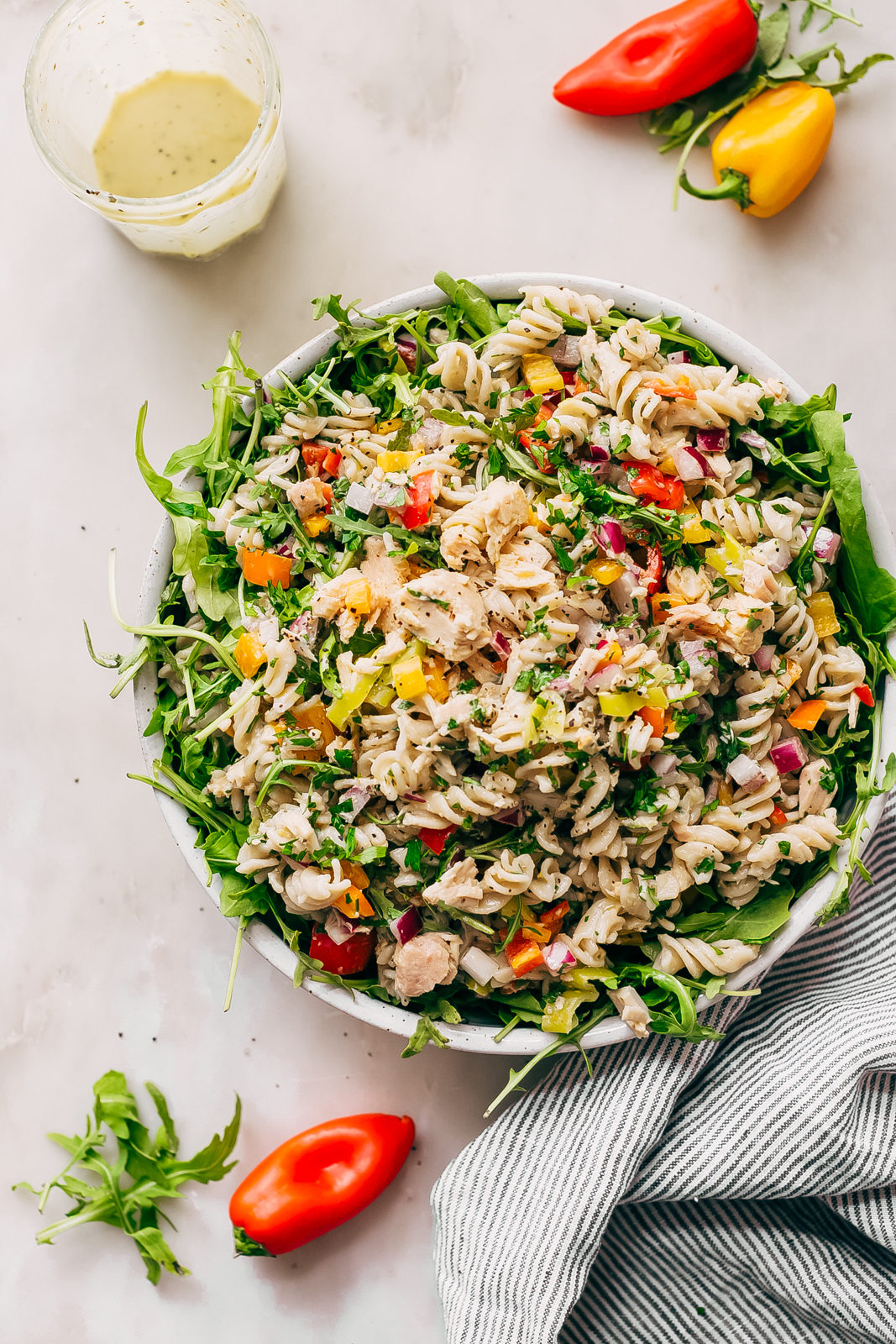 speckled bowl with arugula topped with tuna pasta salad on white marble surface