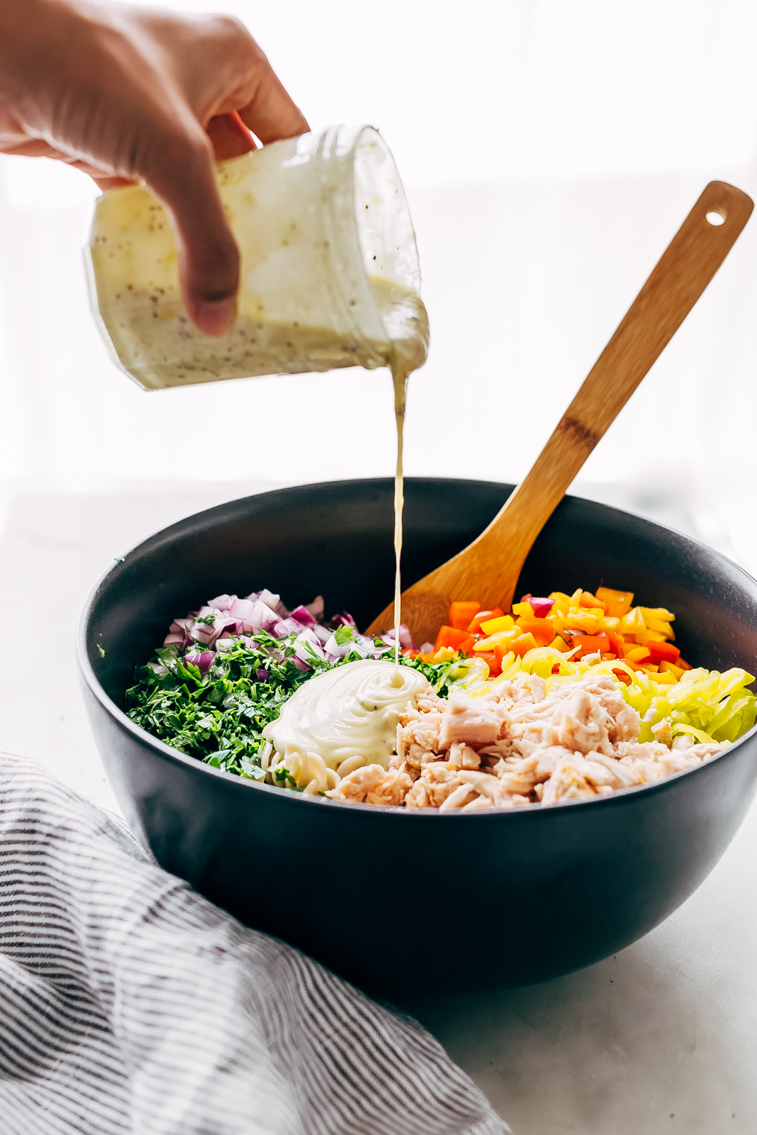 dressing being poured into bowl with salad ingredients