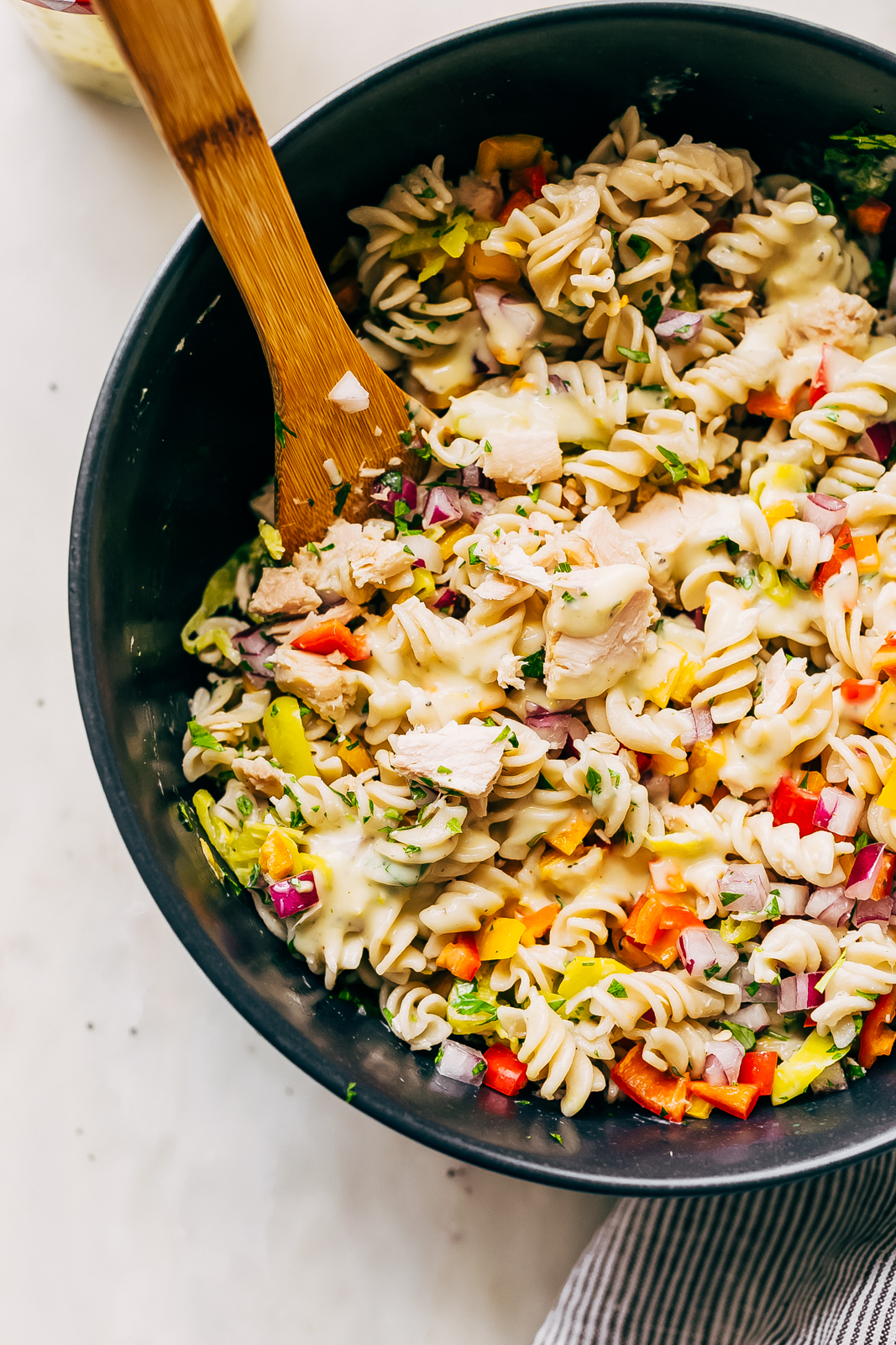 tuna pasta salad in black bowl with wooden spoon