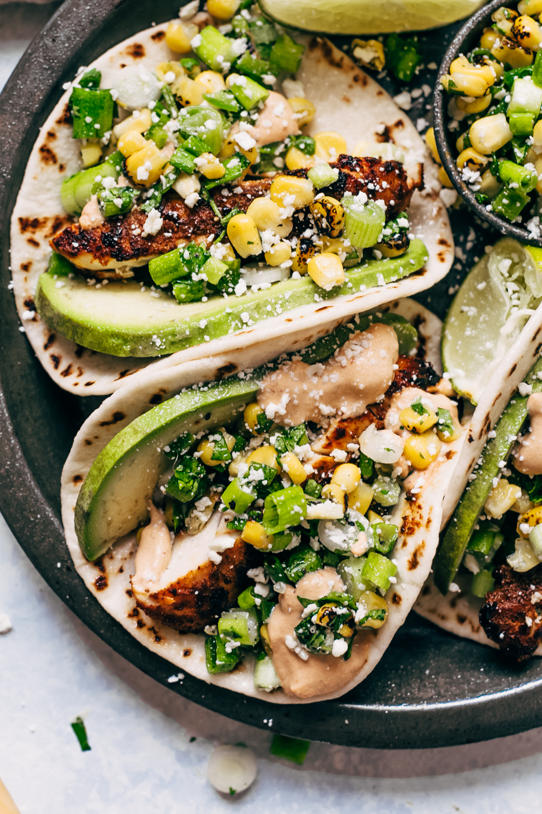 close up of tacos showing chicken, corn, scallions, avocados, topped with cotija cheese