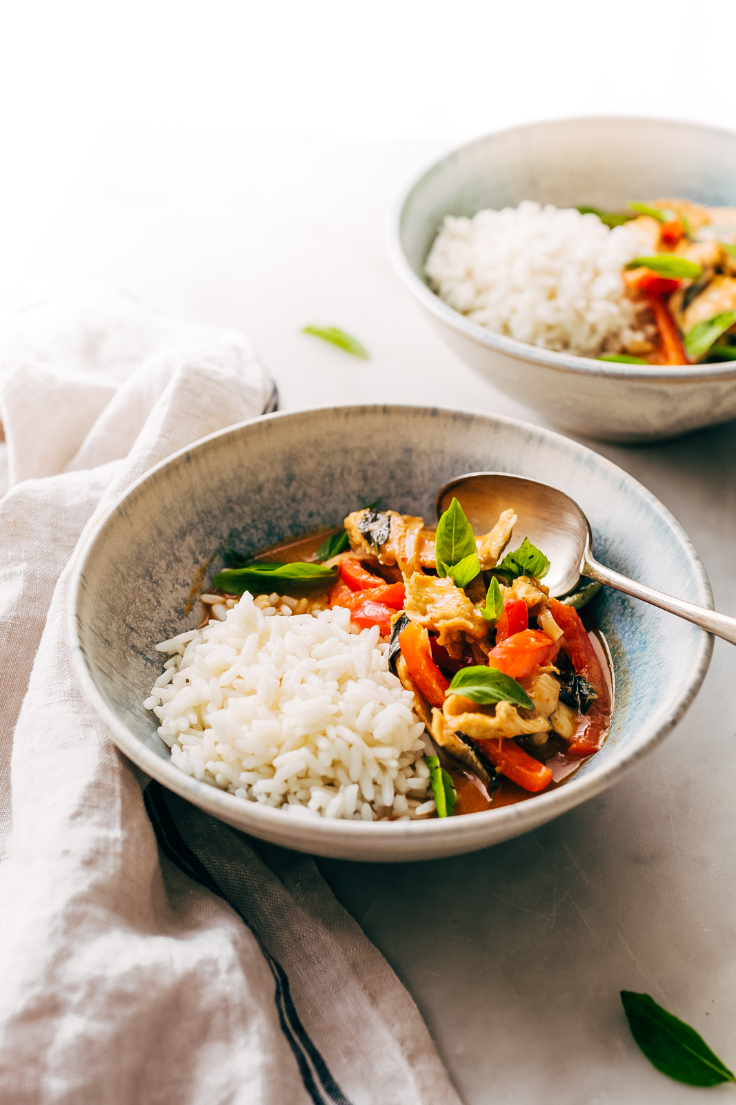 side shot of bowls of prepared curry with rice on white marble