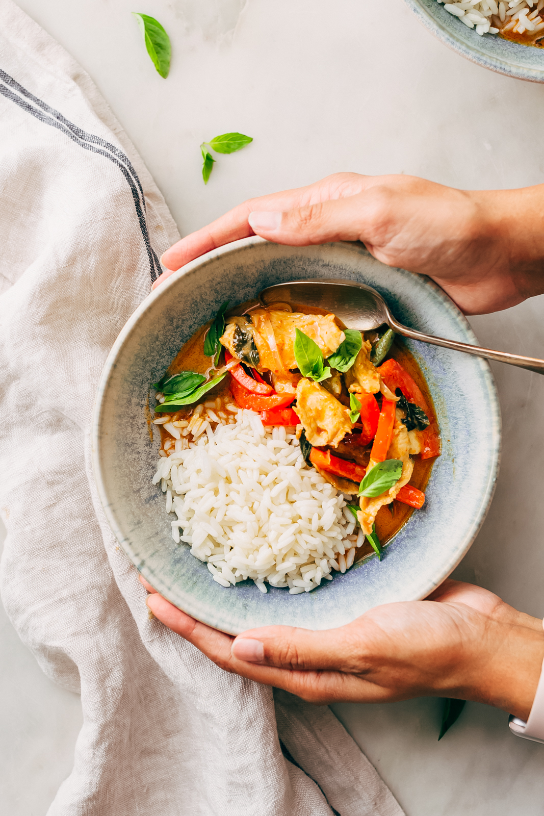 hands holding bowls with rice and panang chicken curry topped with fresh basil