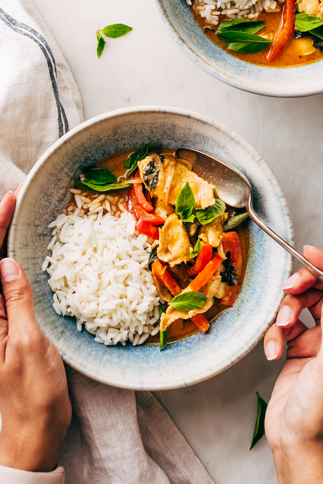 panang curry in bowl with rice white with hands grabbing some on a spoon