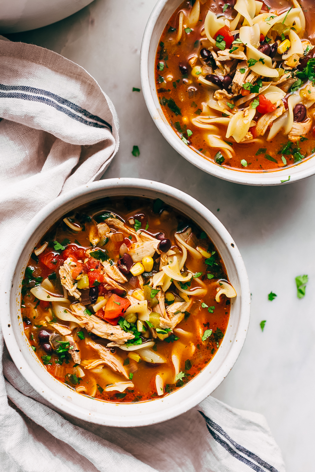 bowls of Mexican chicken noodle soup with striped kitchen towel on white marble