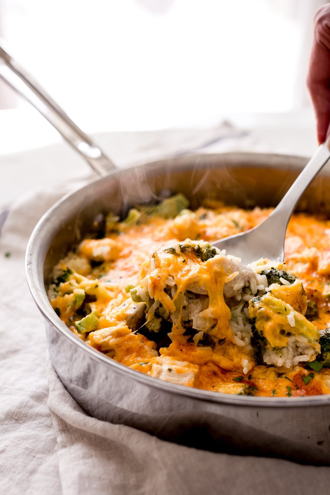 lifting a spoonful of casserole with melted cheese and broccoli showing