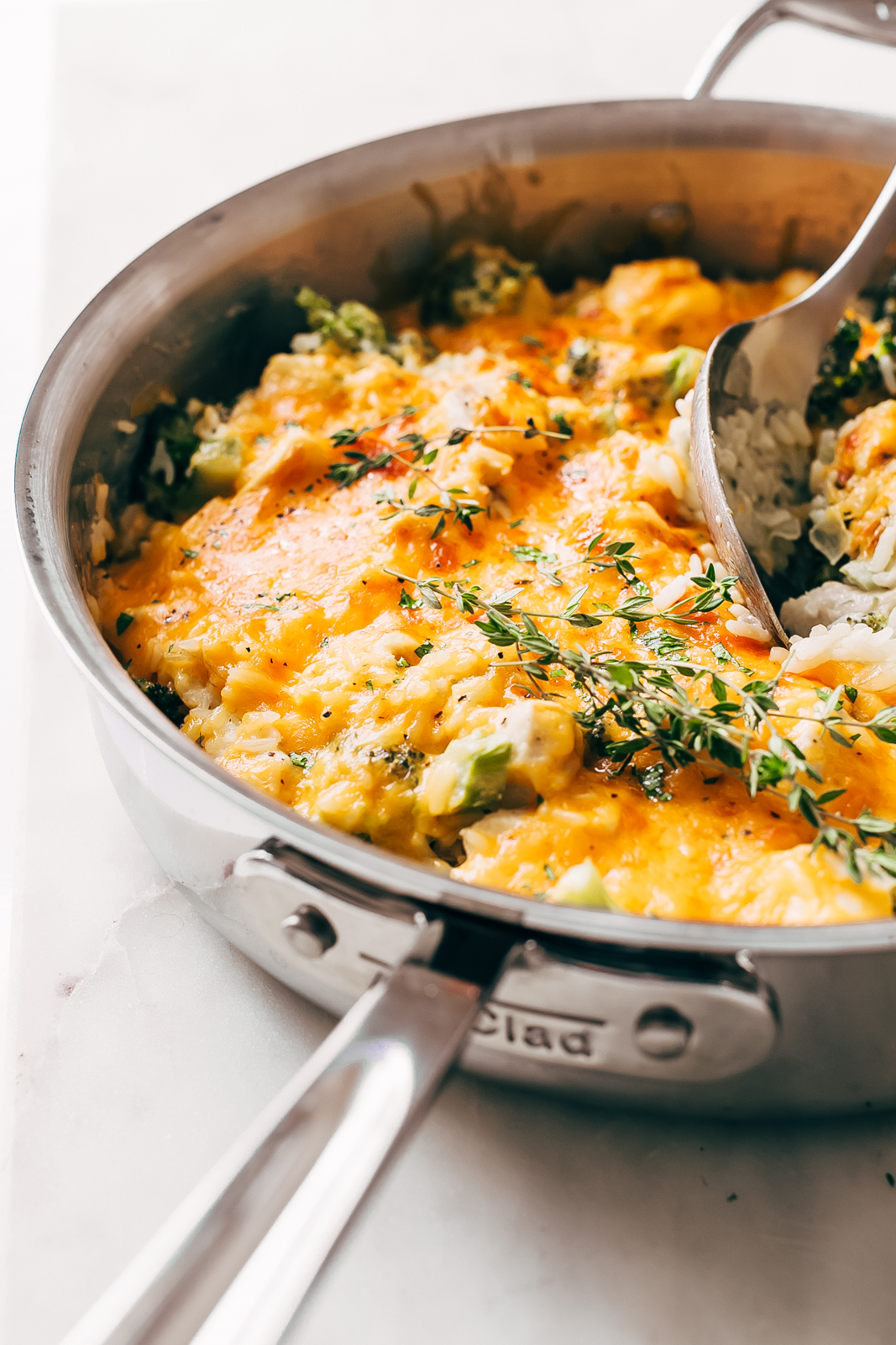 melted cheese on chicken broccoli rice casserole in stainless steel pan
