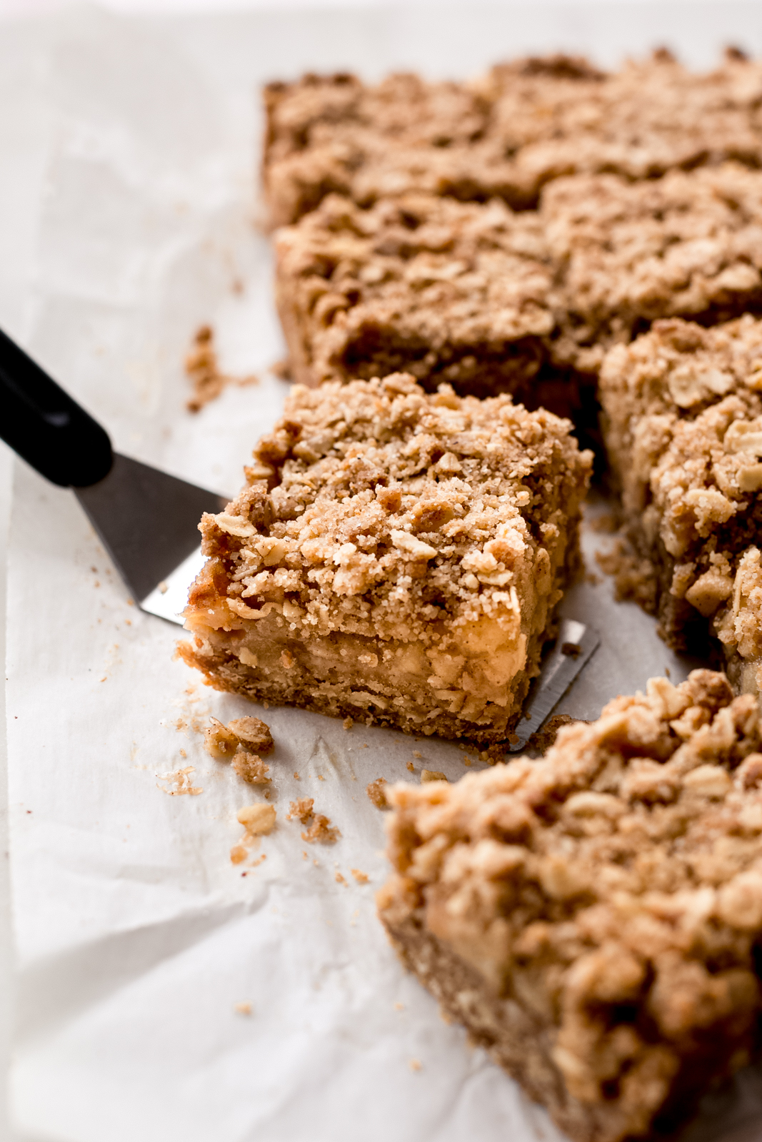 a crumble bar on spatula on white parchment paper