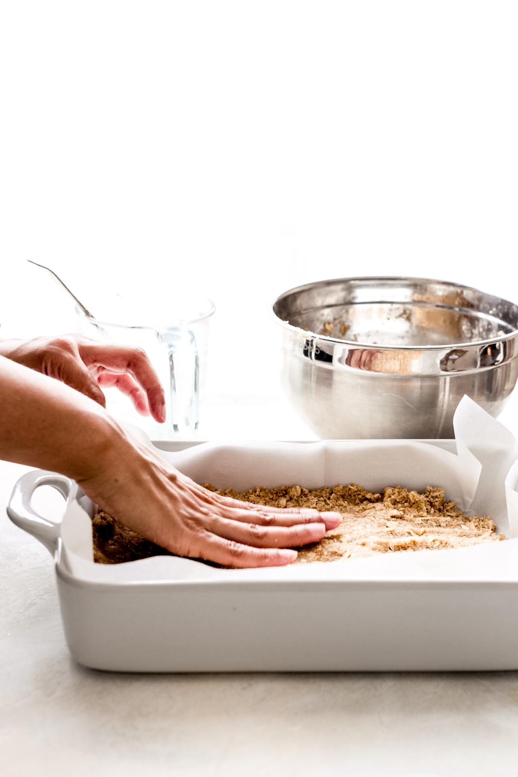 hand pressing bar crust in white baking dish