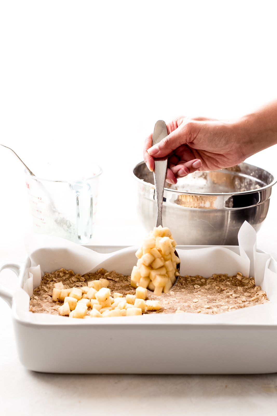 hand with spoon sprinkling diced apples over crust in white baking dish