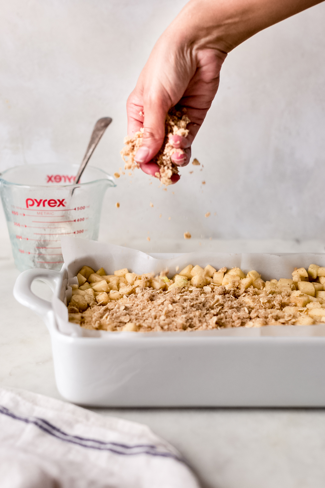 sprinkling crumble mixture over diced apples in white baking dish