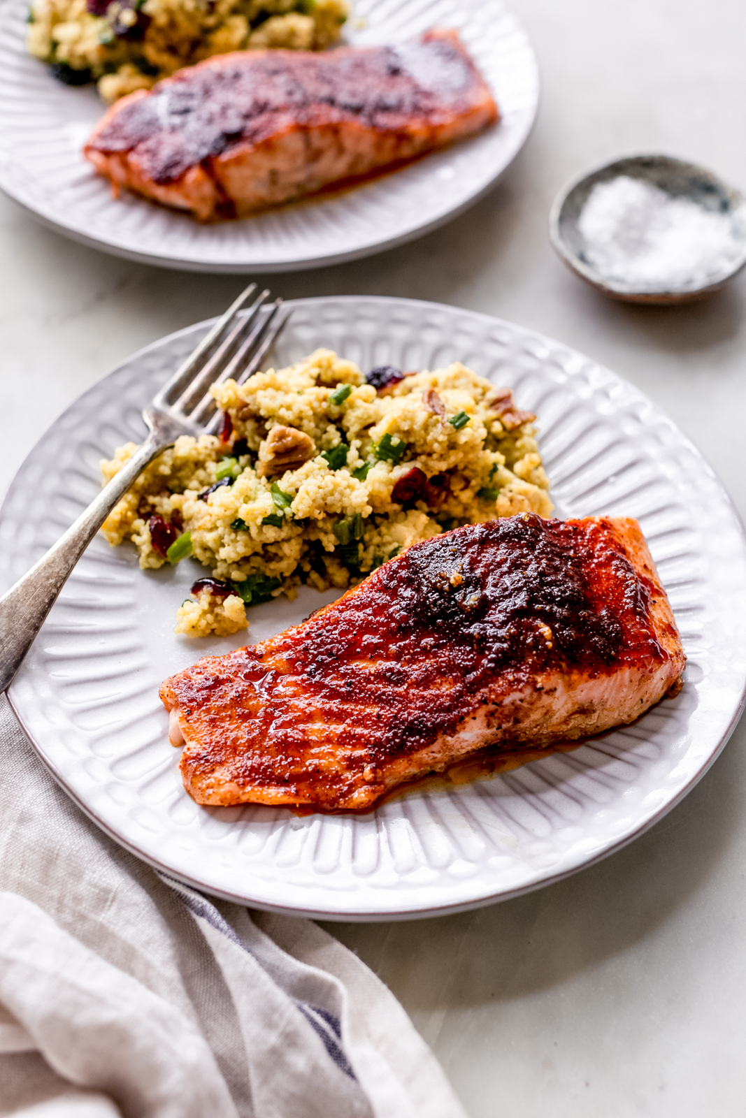 fluted plate with cayenne blackened salmon with curry couscous salad and fork