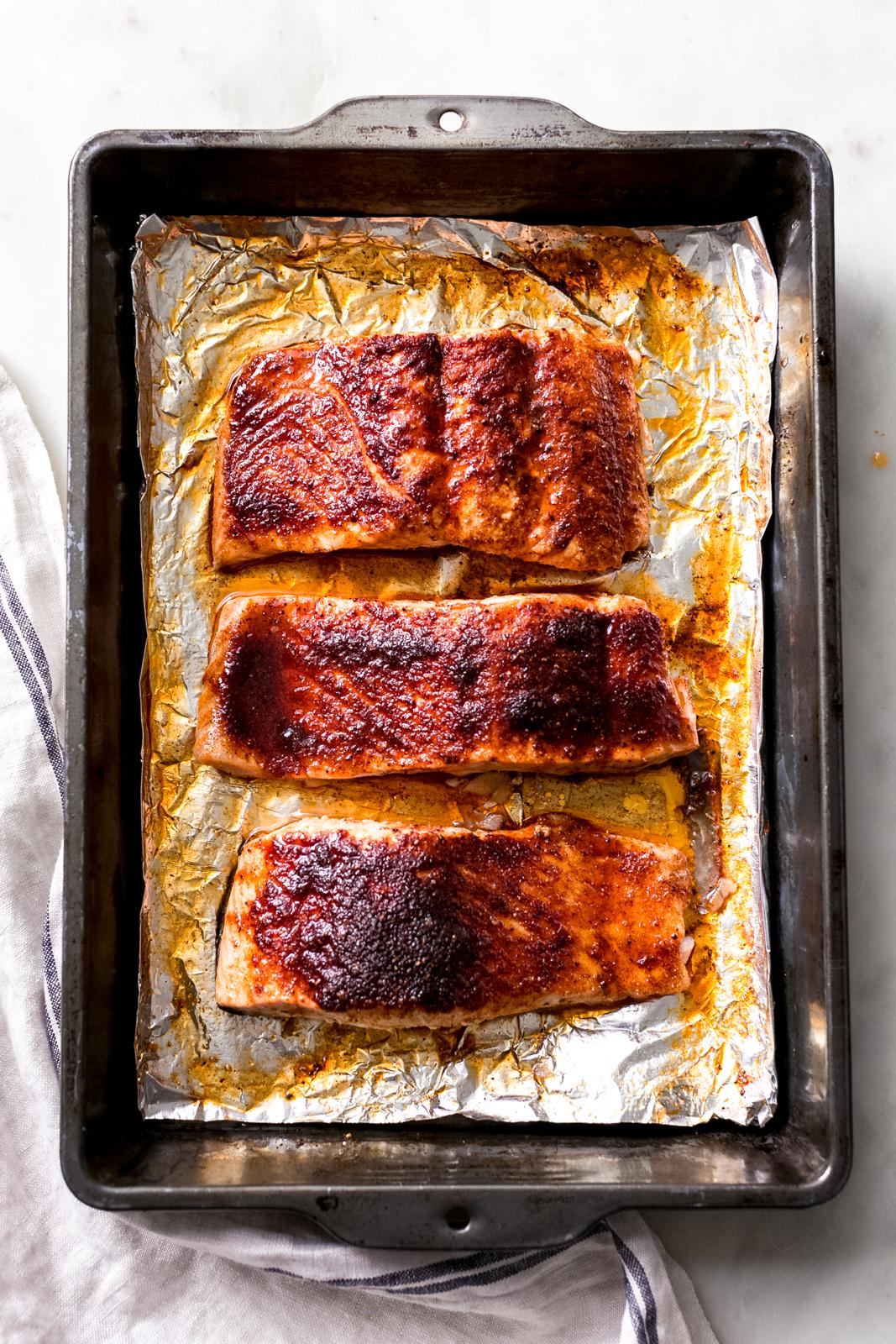 maple glazed salmon portions on foil in baking pan