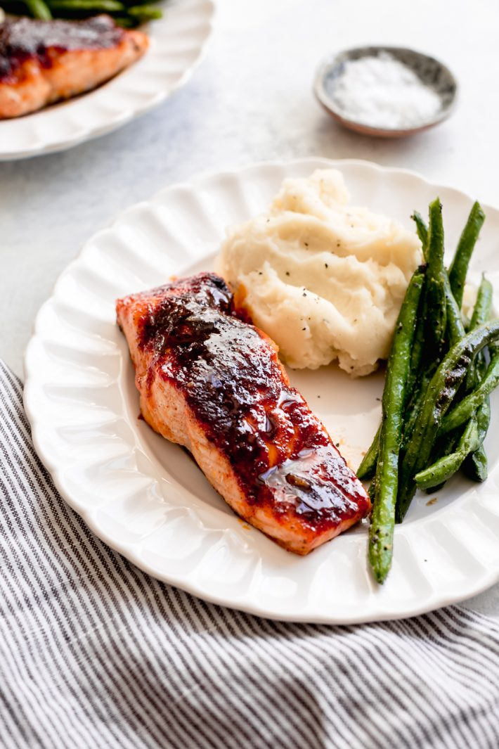 prepared maple glazed salmon filet with green beans and mashed potatoes on fluted plate