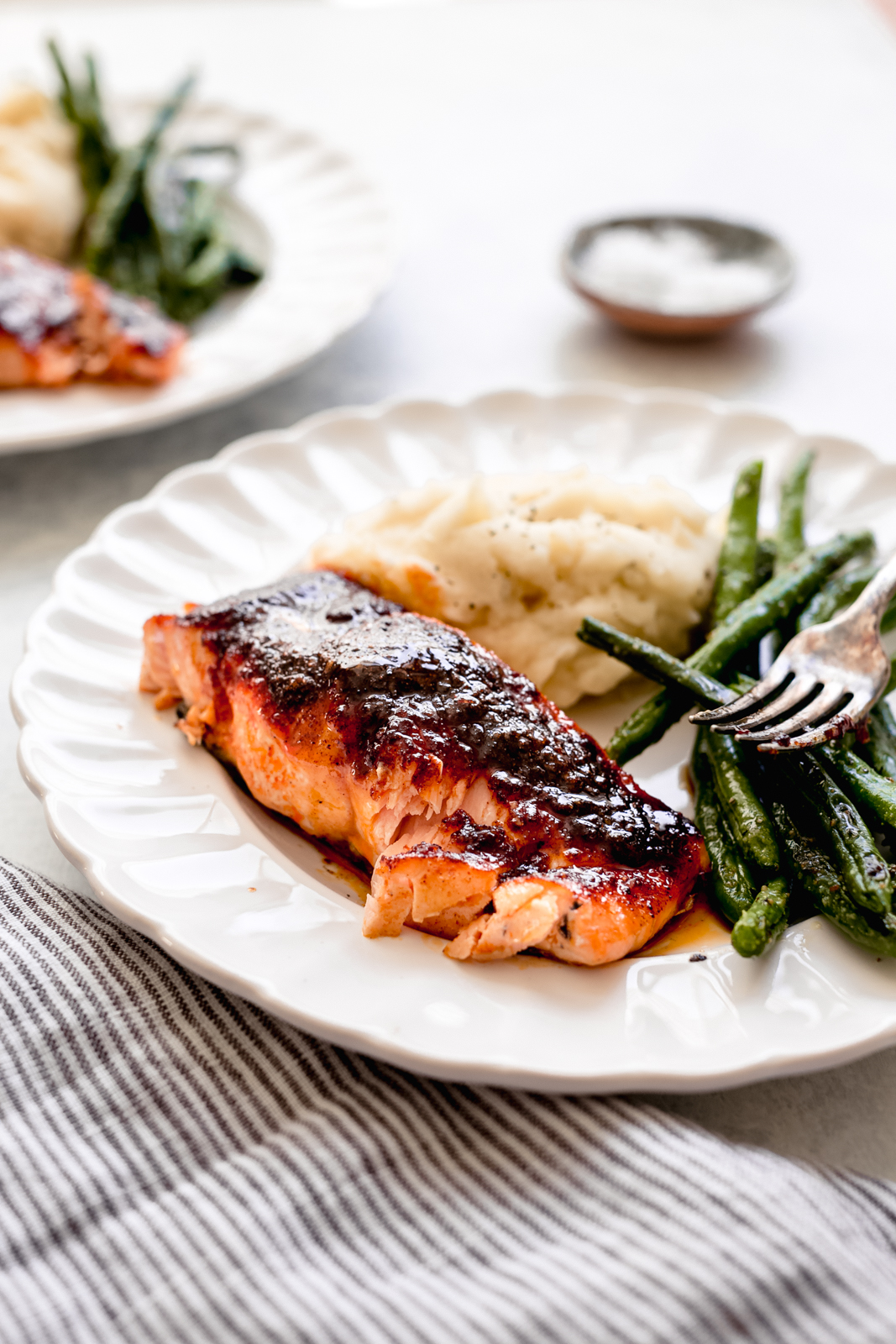 flaked salmon filet on fluted plate with sautéed beans and mashed potatoes