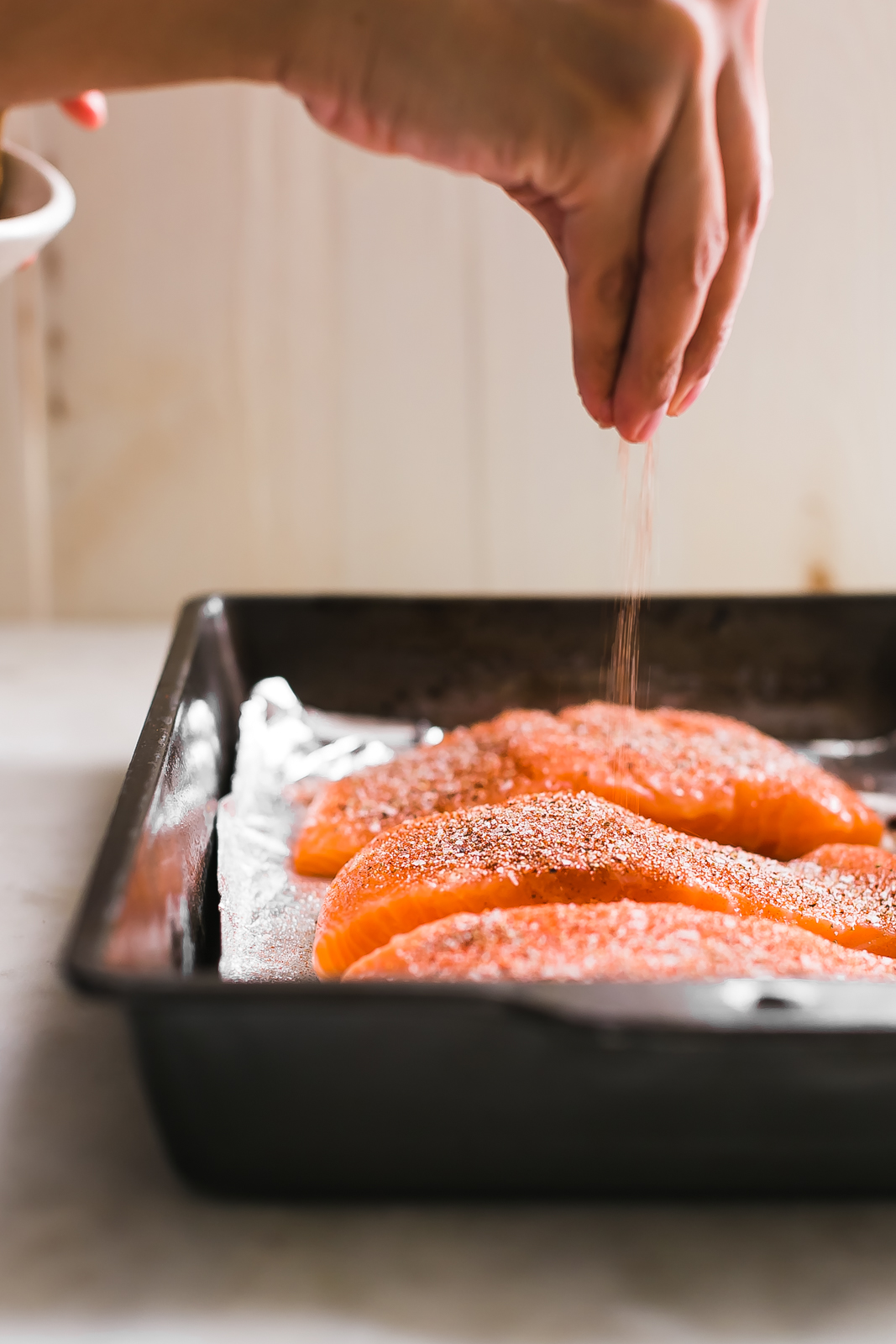 sprinkling seasoning on raw salmon filets plated in metal baking dish
