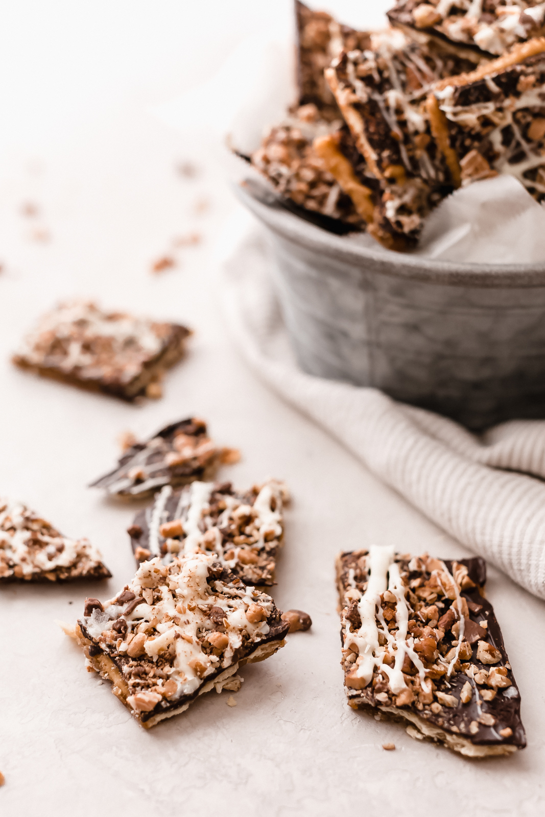 pieces of broken toffee bark on grey surface with galvanized bucketful in the back