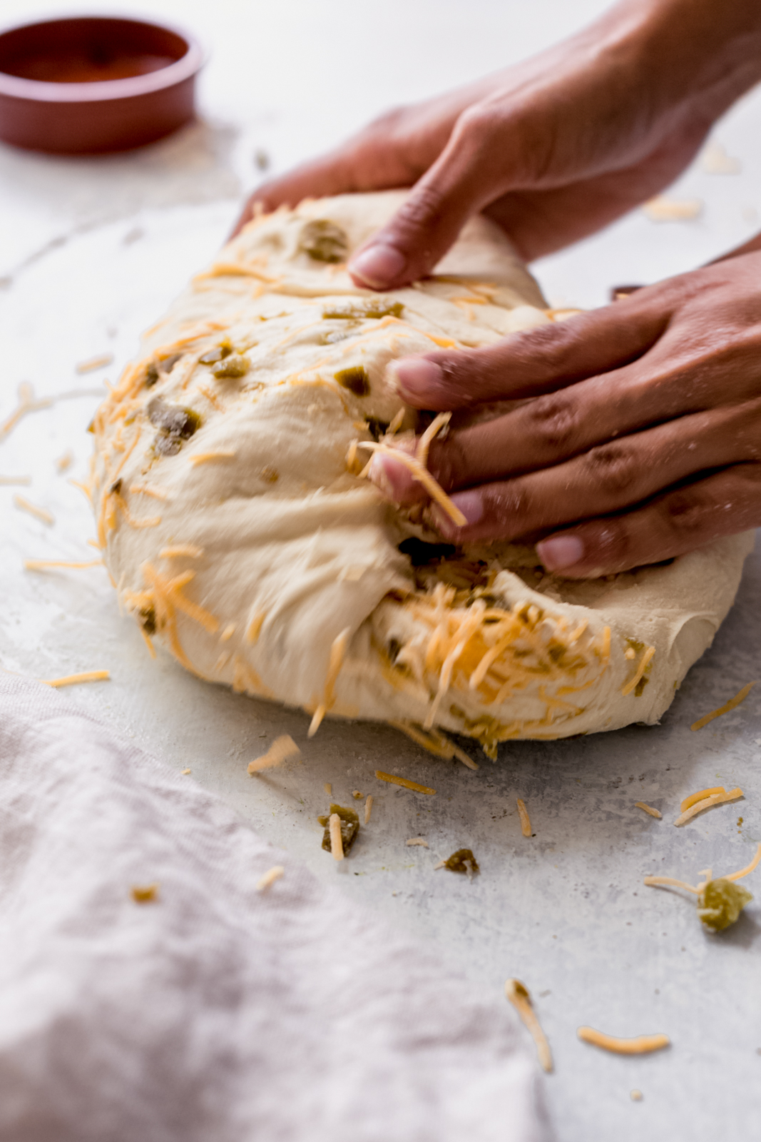 hands rolling and incorporating ingredients into bread dough