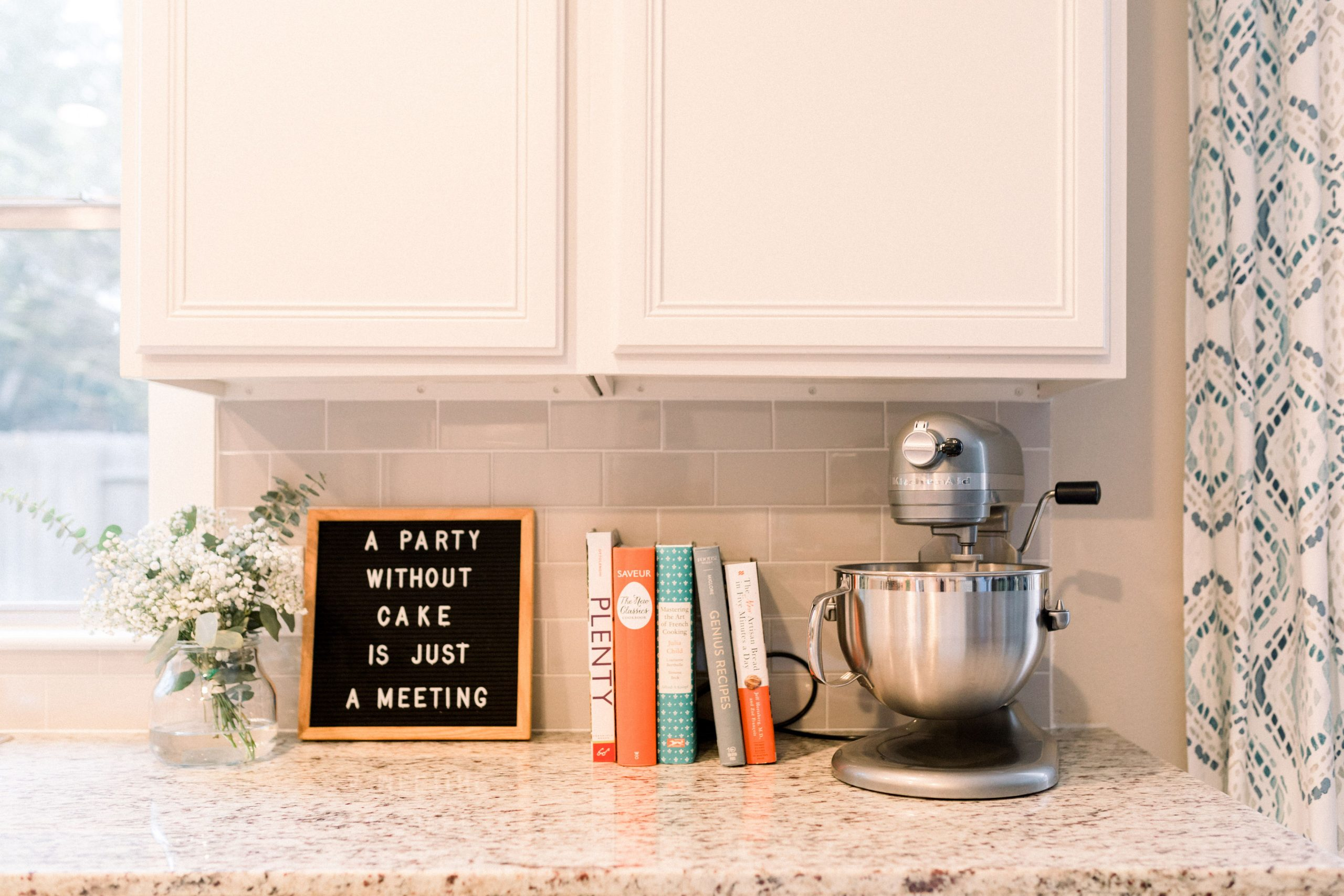 "kitchen picture with books, stand mixer, and sign that read ""a party without cake is just a meeting'"