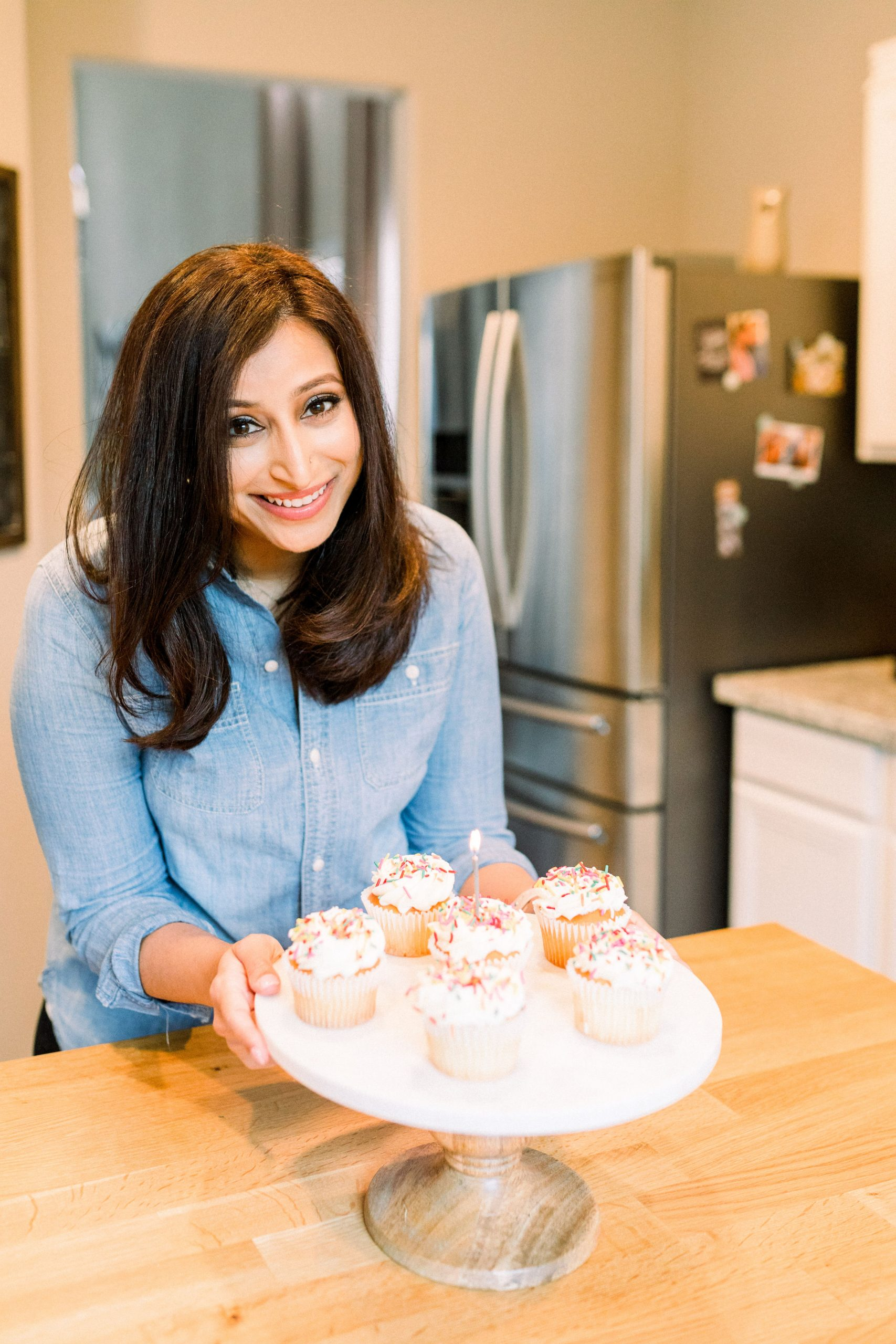 me smiling at the camera holding a cake stand with cupcakes