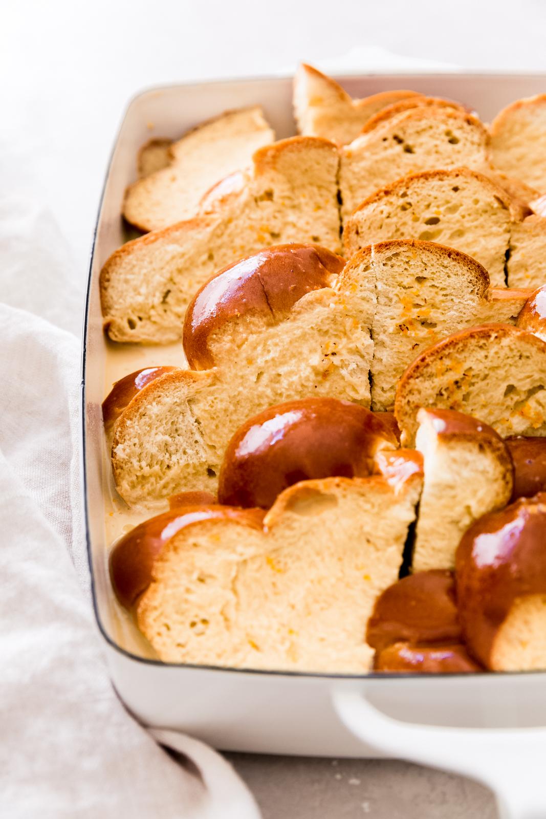 custard soaked brioche bread slices in white baking dish