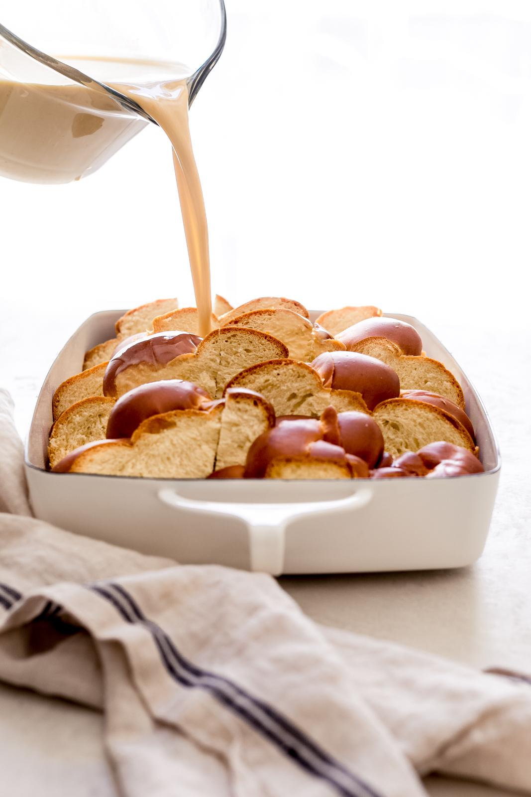 pouring vanilla custard over slices of brioche bread in white baking dish
