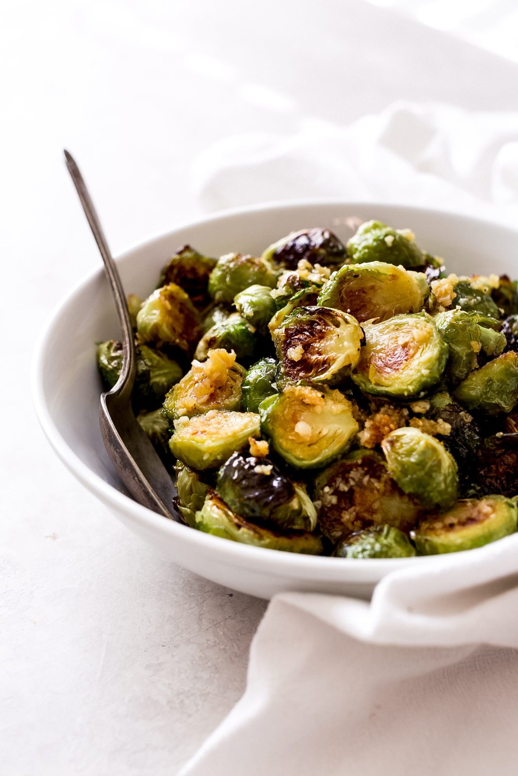 side shot of roasted Brussels sprouts in white bowl with spoon on grey surface with white tea towel