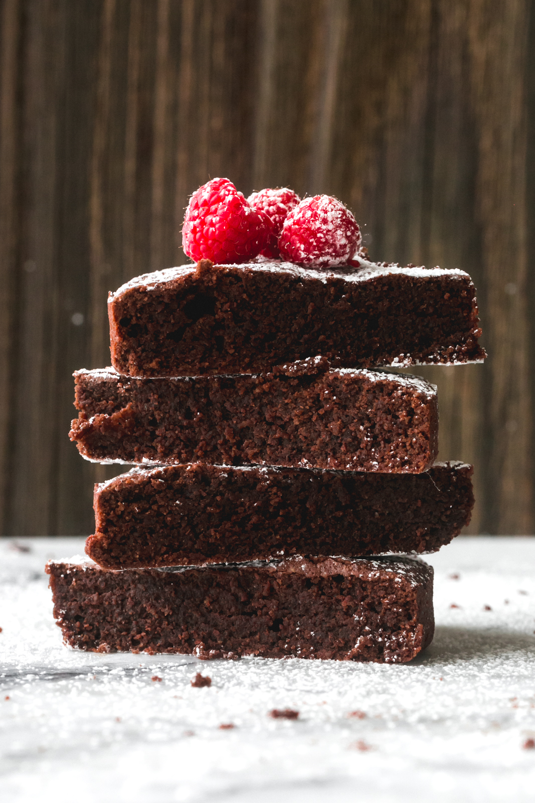 stack of Caprese cake slices dusted with powdered sugar and topped with fresh raspberries