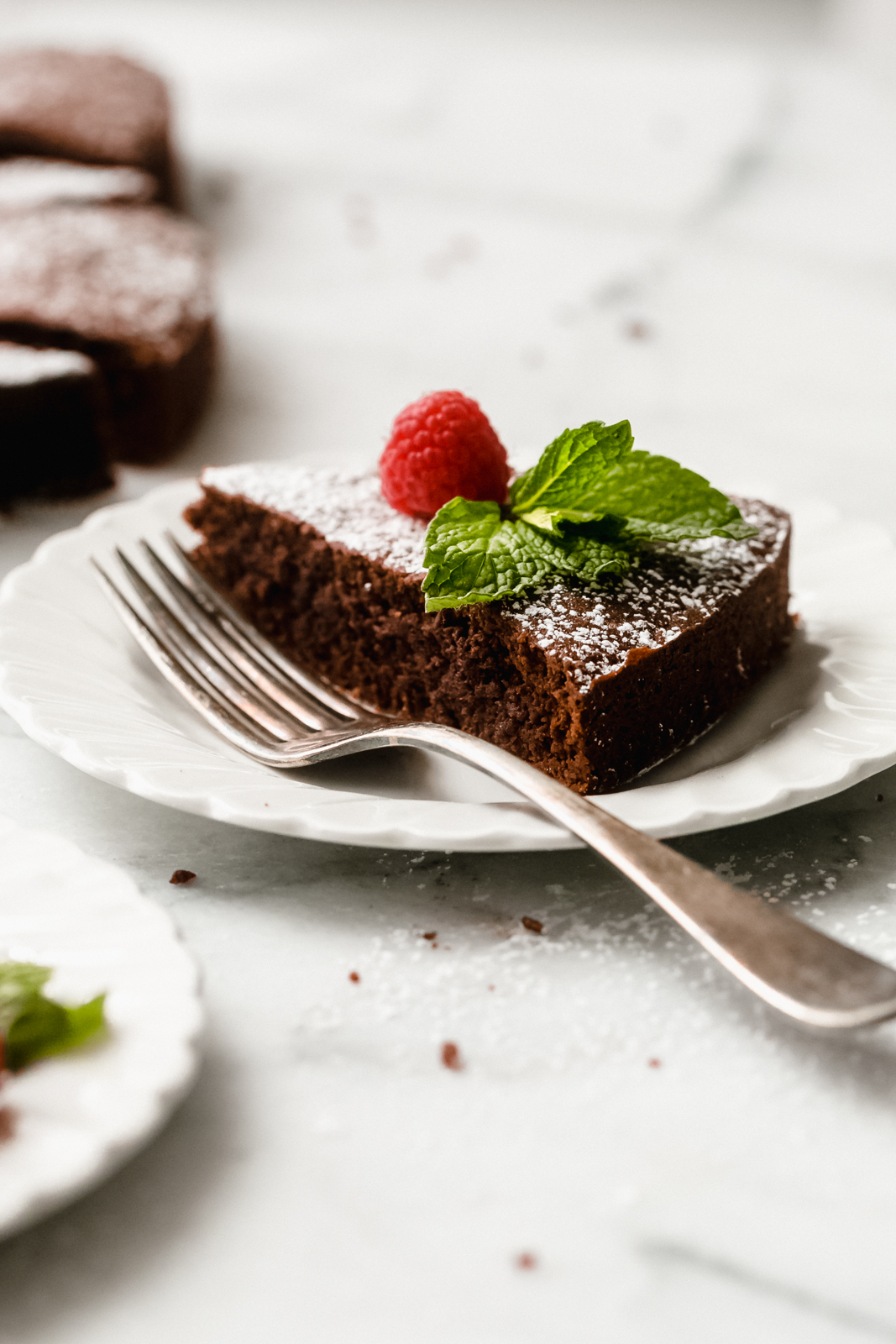 plate with fork and a slice of chocolate cake topped with powdered sugar, raspnberry, and mint