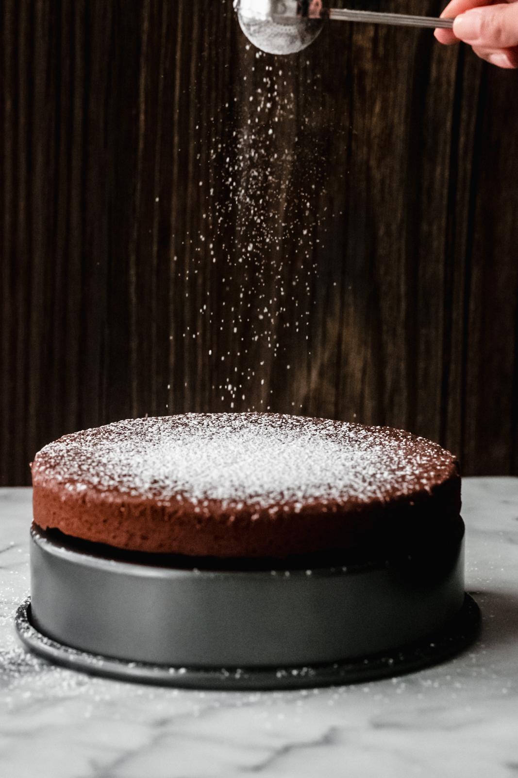 dusting prepared Torta Caprese with powdered sugar from a sugar wand