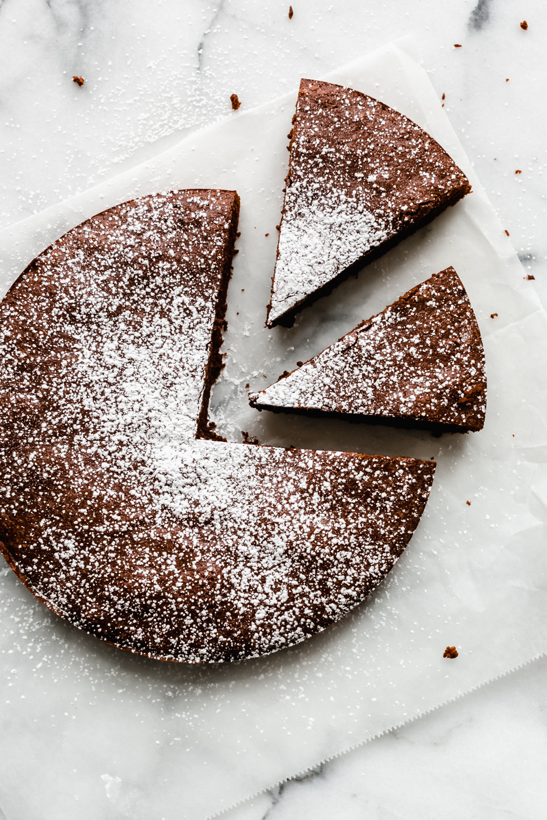 prepared flourless chocolate cake on parchment paper dusted with powdered sugar with two slices cut out
