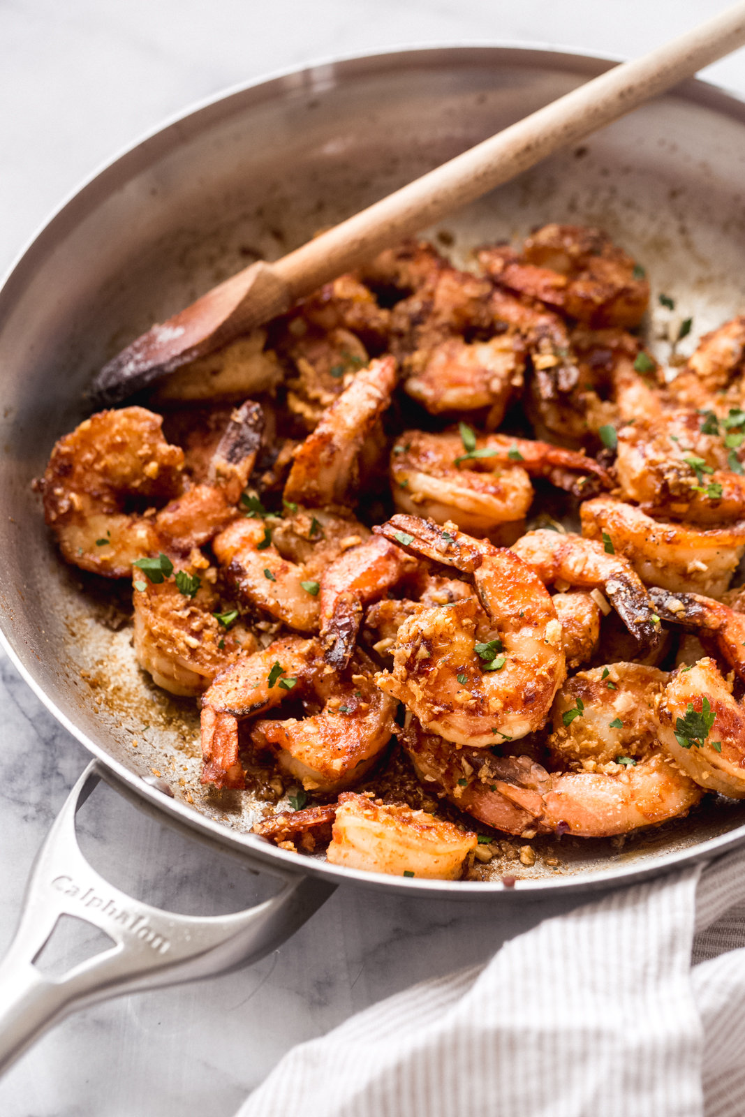 skillet with prepared Hawaiian shrimp scampi with wooden spoon resting