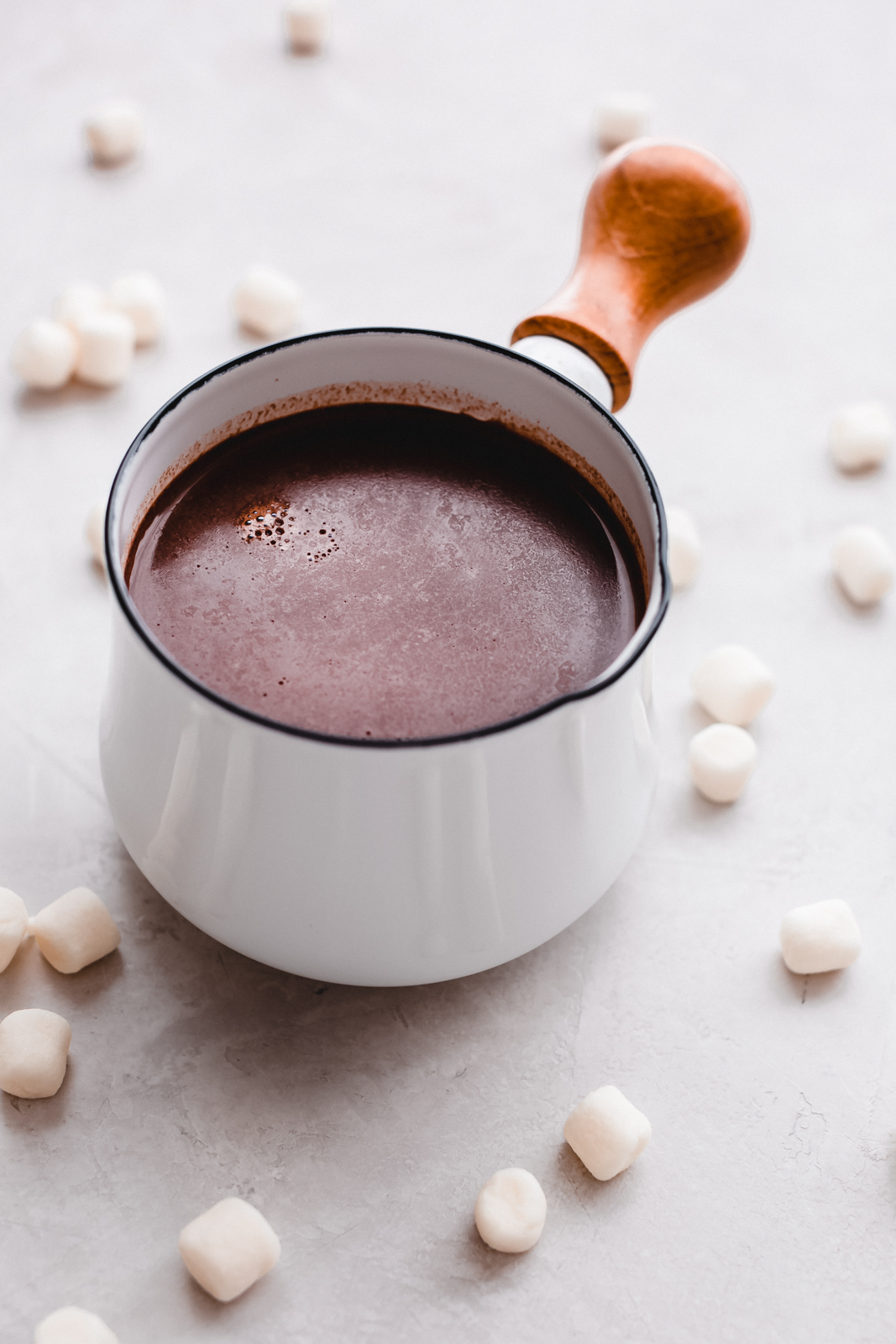 hot chocolate for two in a white saucepan with wooden handle