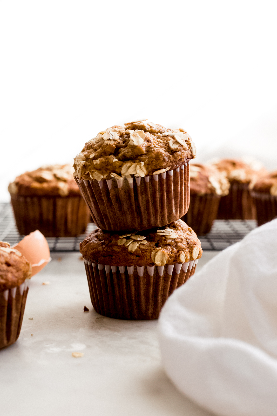 stack of two banana nut muffins with more muffins on wire rack in the back
