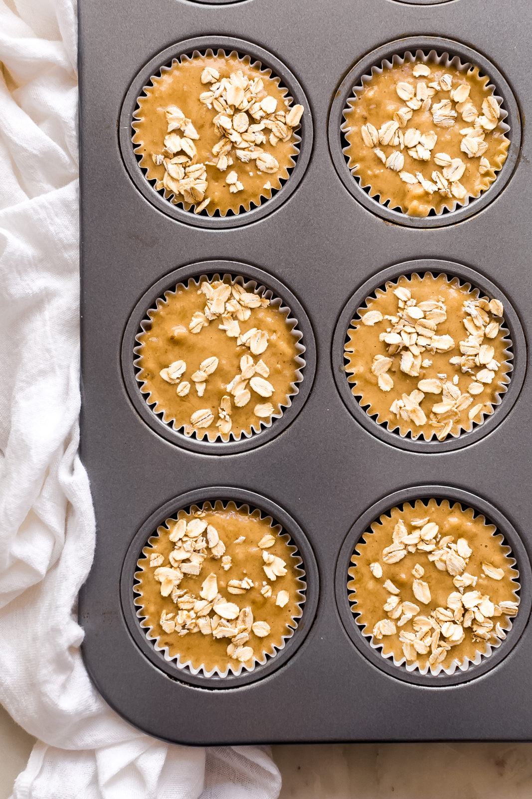 muffin pan lined with liners and filled with banana nut muffin batter topped with oats