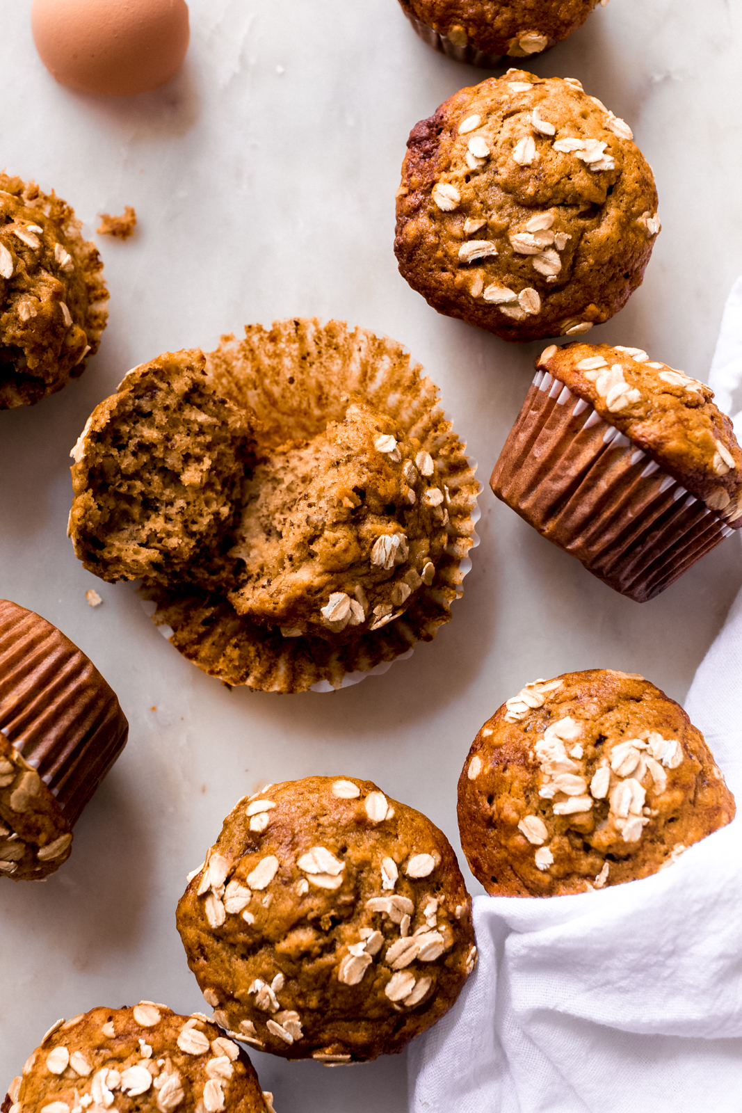 scattered banana nut muffins on white marble with one broken open to show texture