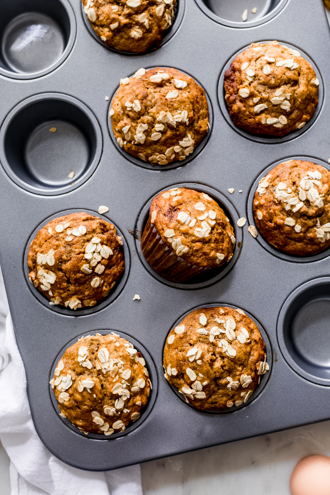 muffin pan with prepared muffins topped with rolled oats