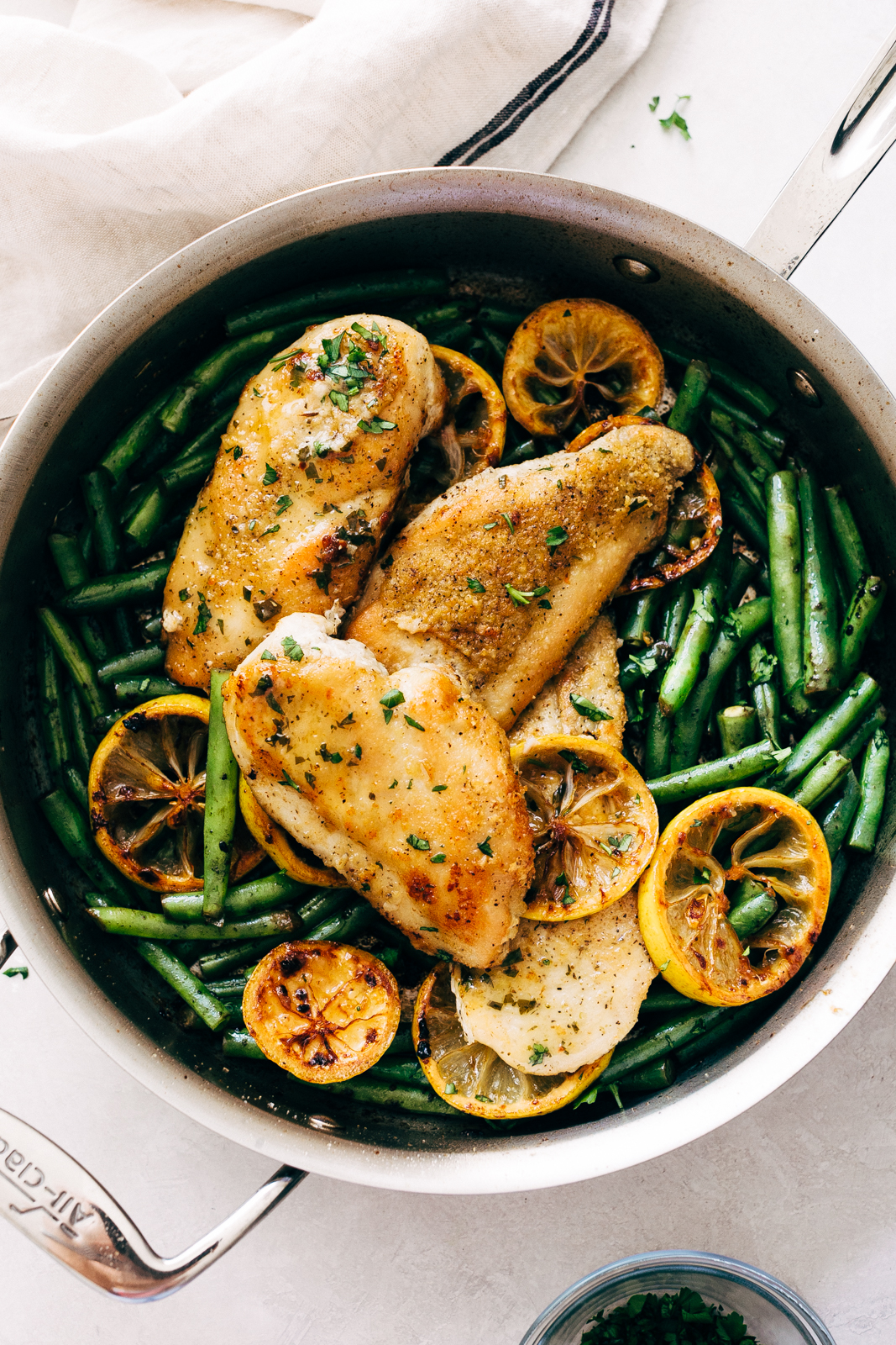 skillet holing sautéed green beans with seared chicken and seared lemon slices
