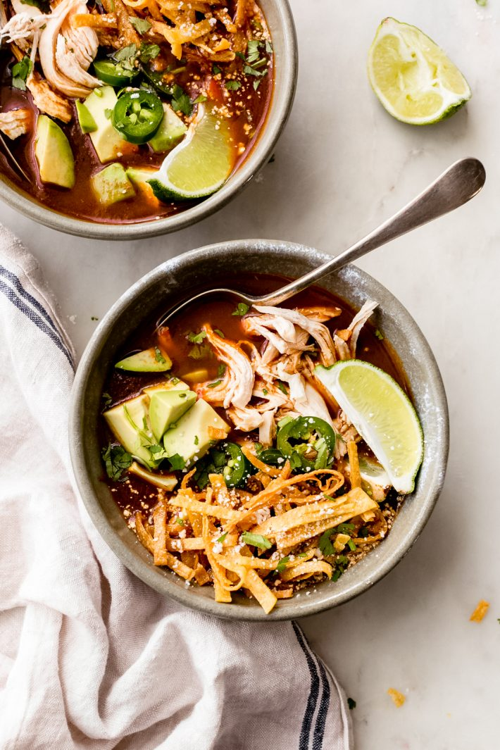 top shot with filled bowls with a variety of tortilla soup toppings