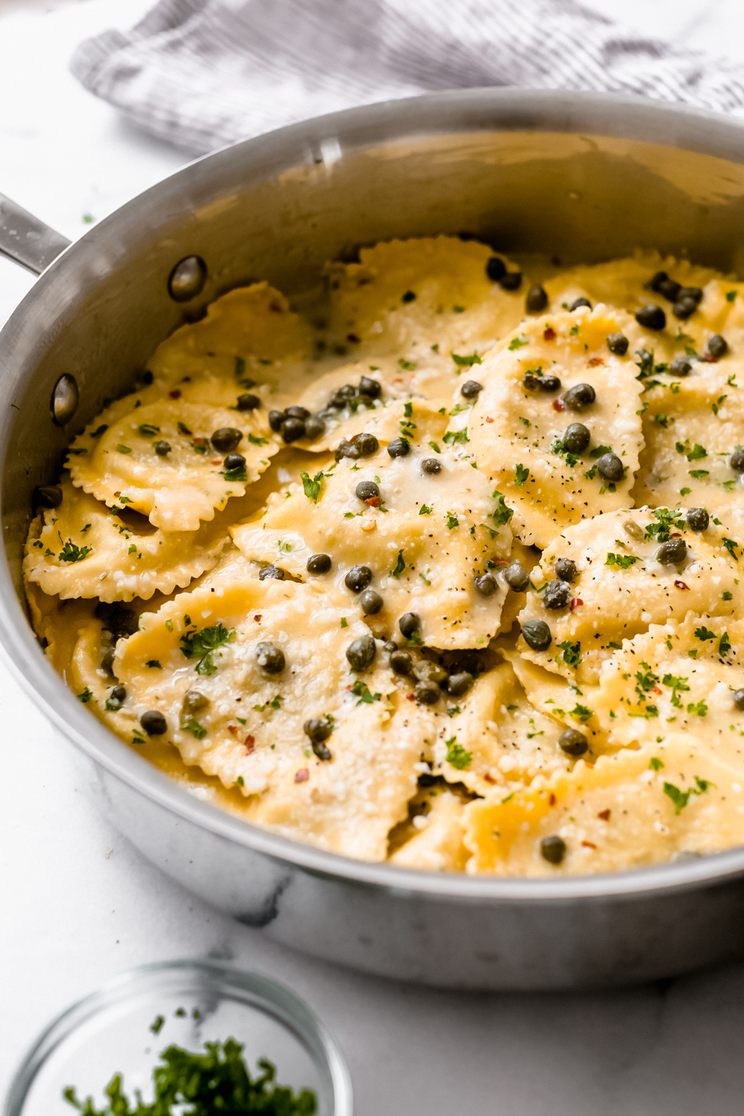 saute pan showing side shot of ravioli in piccata sauce