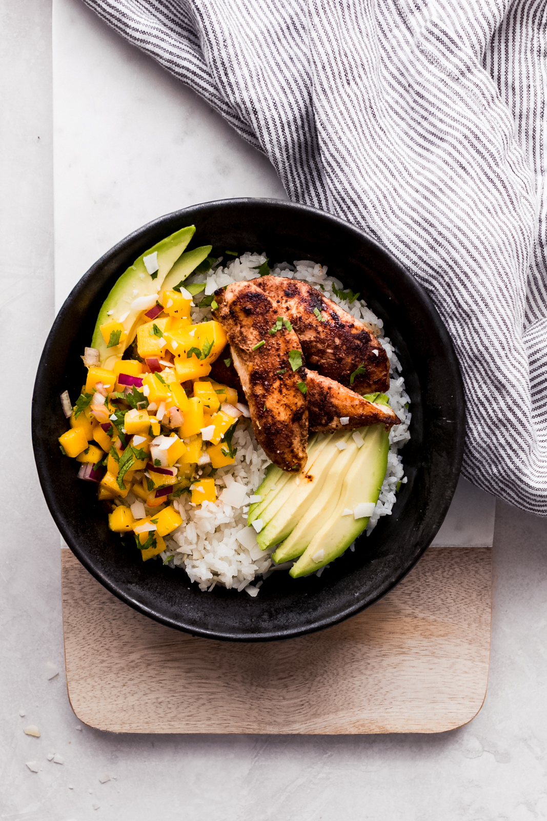 bowl of jerk chicken, rice , topped with mango salsa and avocado slices on marble surface
