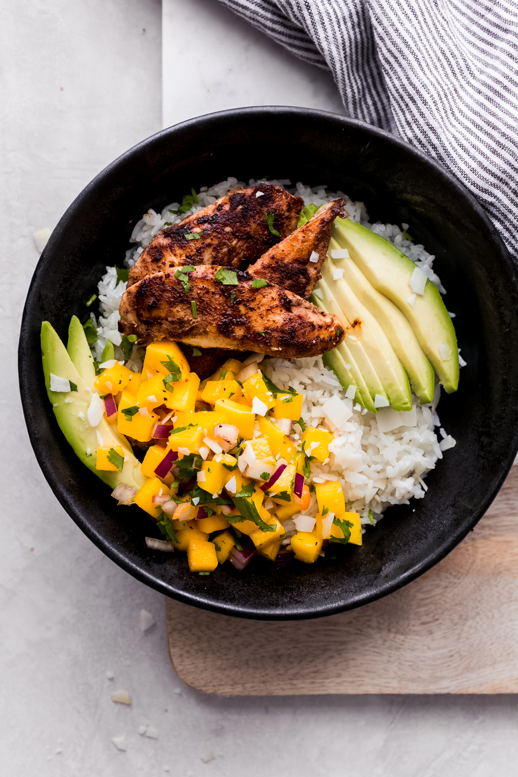 prepared rice topped with mango salsa, jerk chicken, and sliced avocados