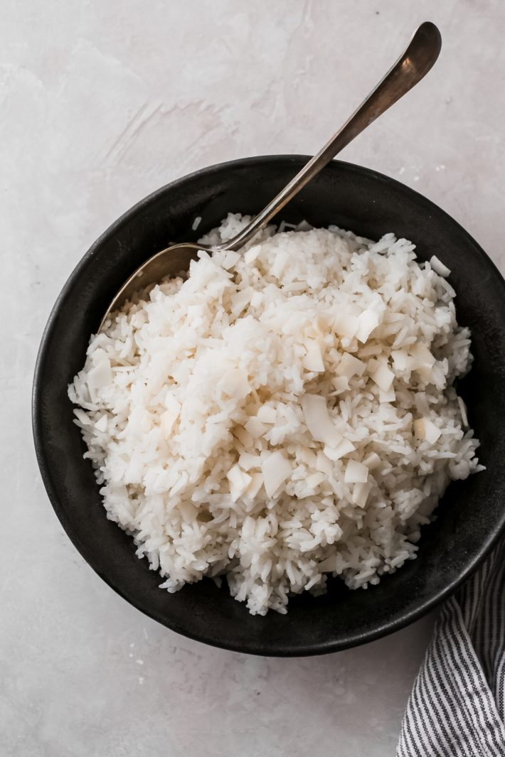 black bowl with prepared coconut rice and a spoon resting in the bowl on grey surface