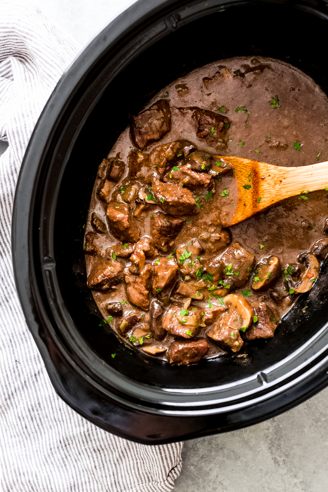 slow cooker insert with prepared beef tips with wooden spoon