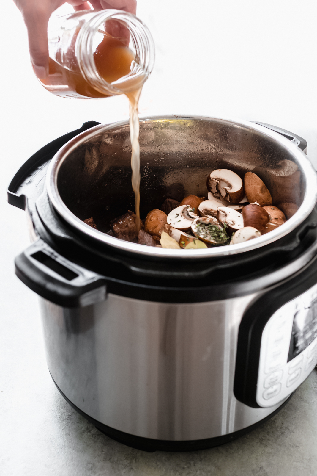 pouring beef stock into the instant pot before pressure cooking the stew