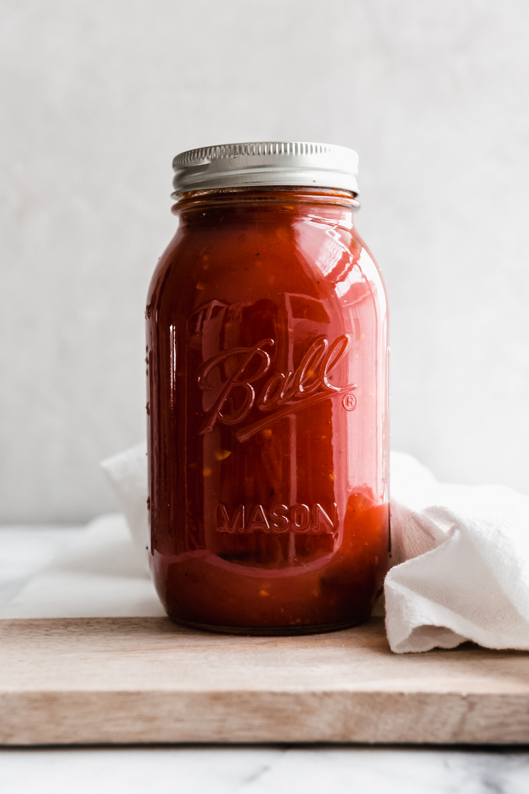 Arrabbiata sauce in glass jar filled and capped on wood surface on marble