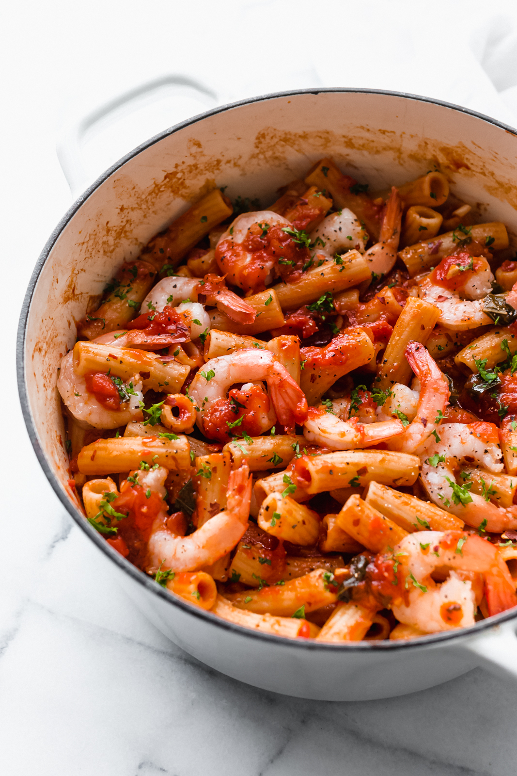 pasta with shrimp tossed with spicy tomato sauce and topped with parsley in cast iron pot
